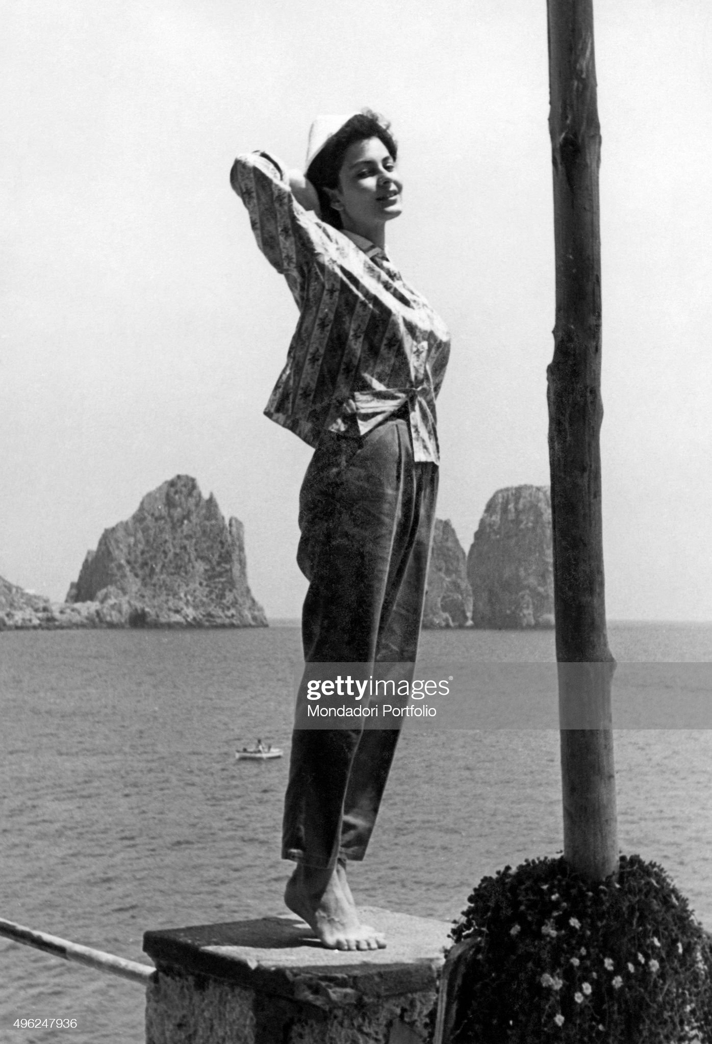 https://media.gettyimages.com/photos/girl-posing-on-a-little-wall-behind-her-the-capri-faraglioni-capri-picture-id496247936?s=2048x2048