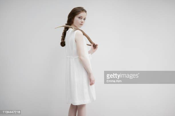 girl posing sideways with antlers - emma white stockfoto's en -beelden