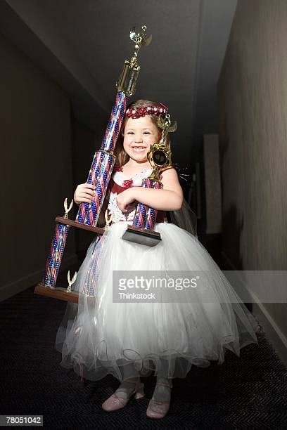 Girl posing with trophies in hallway