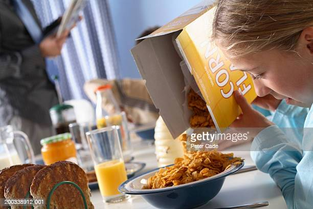 Girl (7-9) pouring cereal into bowl at breakfast table