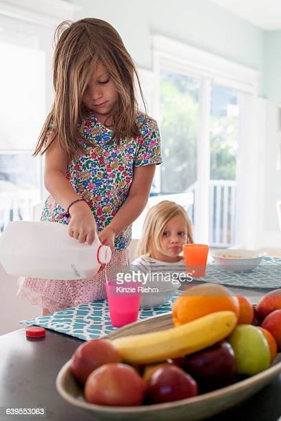 Girl pouring milk into plastic cup
