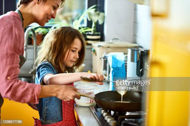 girl pouring pancake batter in frying pan, with mother - making stock pictures, royalty-free photos & images