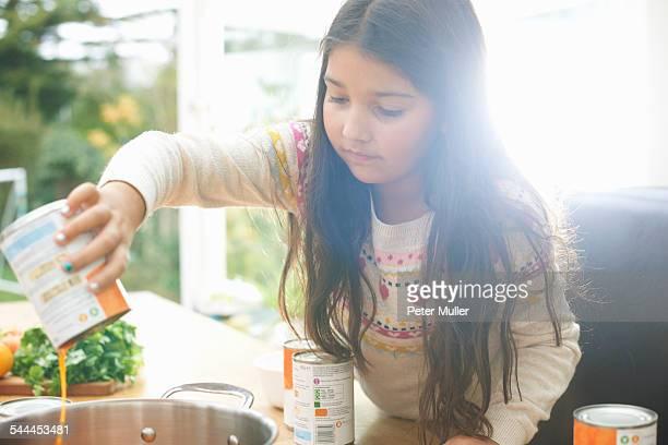 Girl pouring tin of tomato soup into saucepan