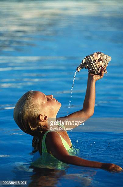 Girl pouring water from conch shell, side view