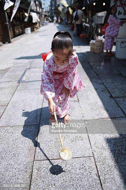 girl (3-5) pouring water on sidewalk with ladle - kazuko kimizuka stock-fotos und bilder