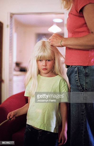 Girl pouting while mother braids her hair