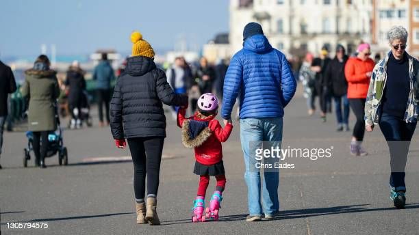 Girl practices her rollerskating as the family take a stroll in the sunshine along Hove seafront on March 07, 2021 in Brighton United Kingdom. The UK...