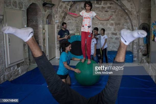 A girl practices walking on a ball during an acrobatics workshop at the Istasyon Sirkhane Center on July 24 2018 in Mardin Turkey The circus school...