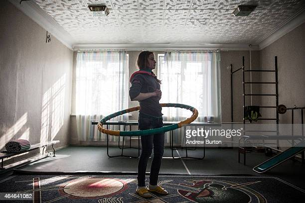 A girl practices with the hoolahoop during gym class at Torez Special Secondary boarding school on February 27 2015 in Torez Ukraine The school acts...