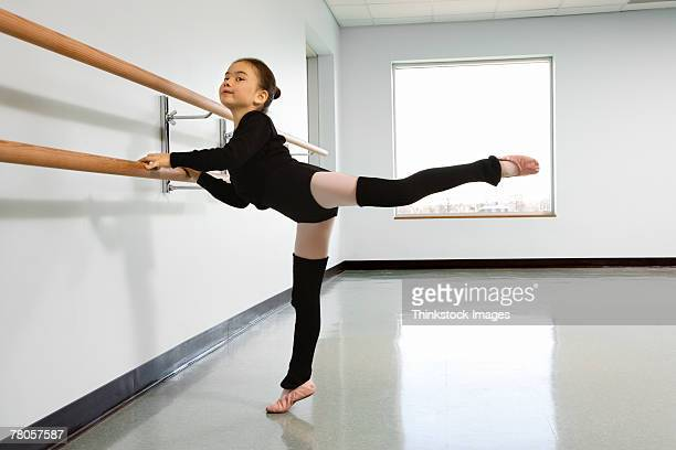 Girl practicing arabesque at the barre in ballet class