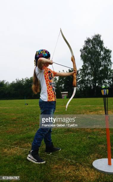 Girl Practicing Archery While Standing On Field In Park