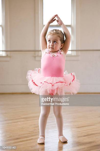 Girl (2-3) practicing ballet in studio