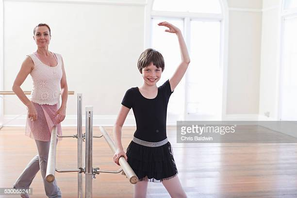 Girl practicing ballet with teacher at the barre in ballet school