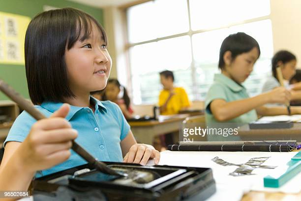 Girl practicing calligraphy in classroom