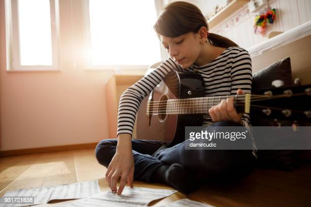 girl practicing guitar at home - practicing stock pictures, royalty-free photos & images