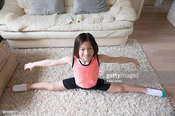 Girl practicing gymnastic splits on living room rug