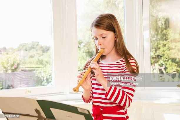 girl practicing playing recorder. - recorder musical instrument stock photos and pictures