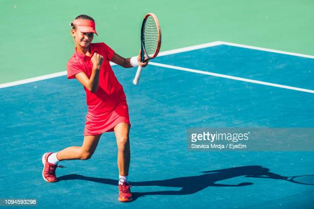 girl practicing tennis while standing in court during sunny day - tennis ストックフォトと画像