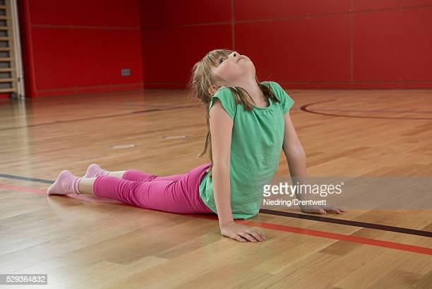 Girl practicing upward facing dog position in sports hall, Munich, Bavaria, Germany