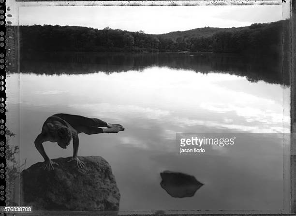 A girl practicing yoga balancing on a rock in a natural setting Photographed in black and white on Polaroid film