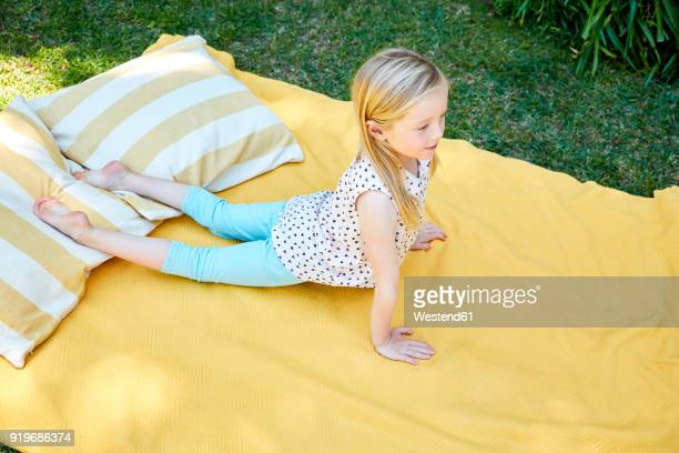 Girl practicing yoga on a blanket