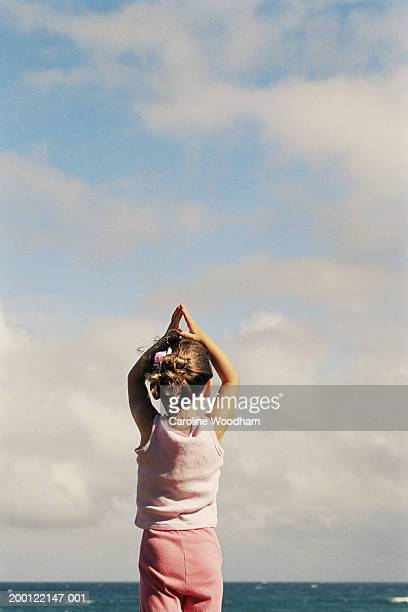 Girl (2-4) practicing yoga on beach, rear view