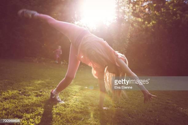 Girl practising cartwheels in a back yard