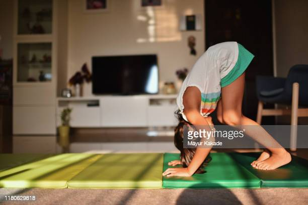 girl practising somersault at home - gymnastiek stockfoto's en -beelden