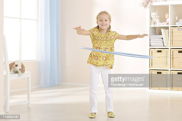 Girl practising with hula hoop, front view
