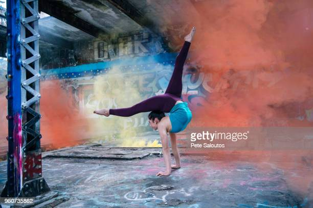 girl practising yoga on outdoor stage - bending over backwards stock photos and pictures