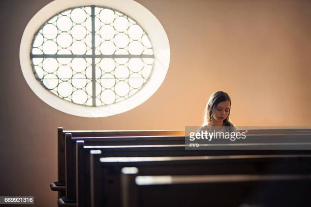 girl praying at the church - kirche stock-fotos und bilder