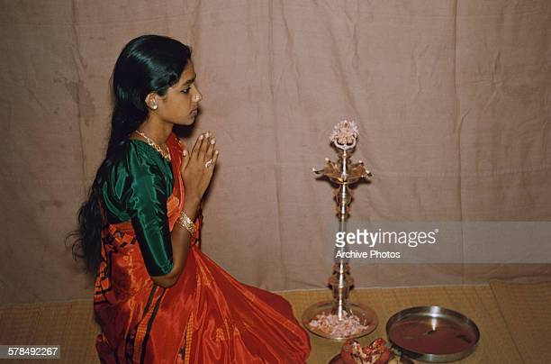 A girl praying during Diwali the Hindu Festival of Lights in India circa 1970
