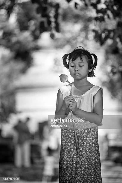 Girl praying in Buddhist temple, holding lotus flowers, Chiangmai, Thailand.