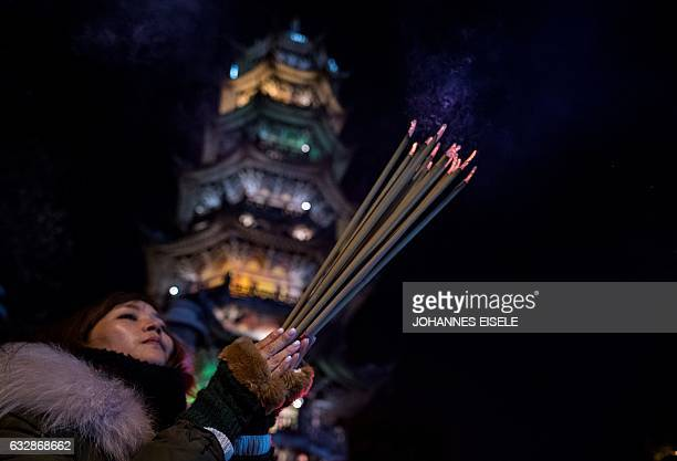 CORRECTION A girl prays with incense sticks at the Longhua temple in Shanghai on January 27 2017 China marks the beginning of the Lunar New Year the...