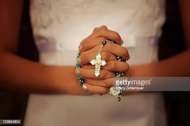 girl prepares for her first communion by praying - rosary beads stock pictures, royalty-free photos & images