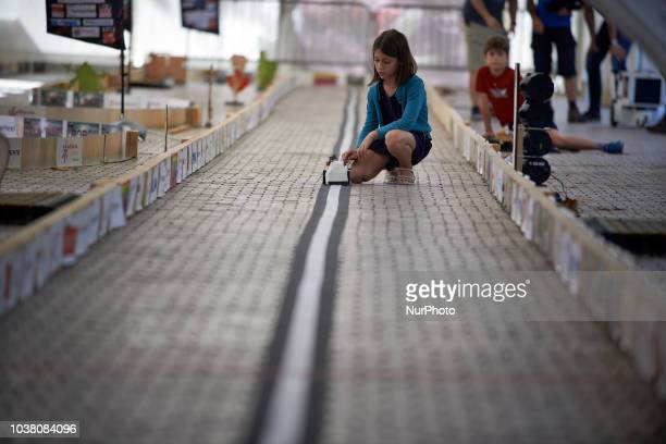 A girl prepares to launch her robot during a try A robots race took place in Toulouse Machines are either cars or walking robots They were supposed...