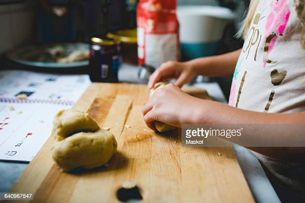 Girl preparing dough on cutting board at kitchen counter