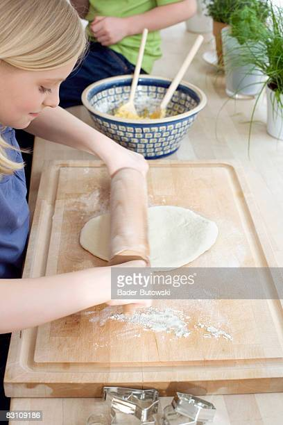 Girl (8-9) preparing dough with rolling pan, high angle view