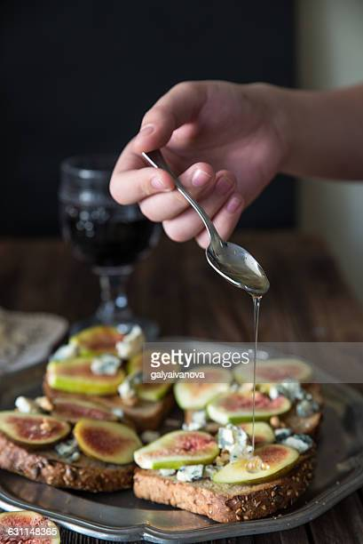 Girl preparing fig and blue cheese open sandwiches