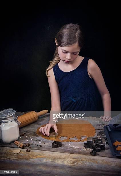 Girl preparing gingerbread cookies