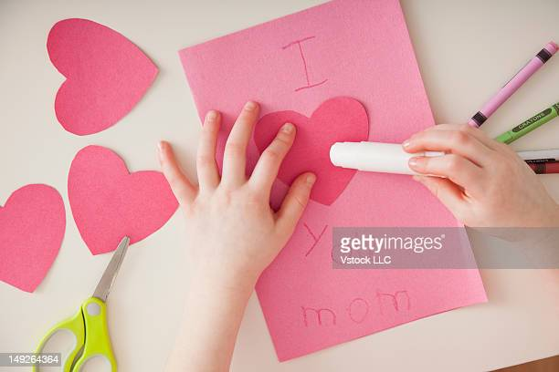 Girl (4-5) preparing greeting card for mother