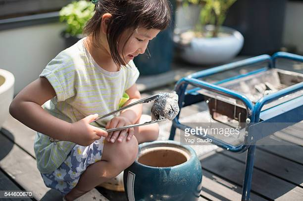 girl preparing the barbecue charcoal - tongs work tool stock photos and pictures