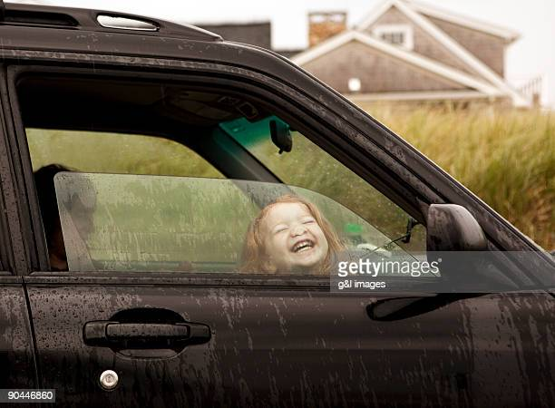girl (2-3) pressing face against car window