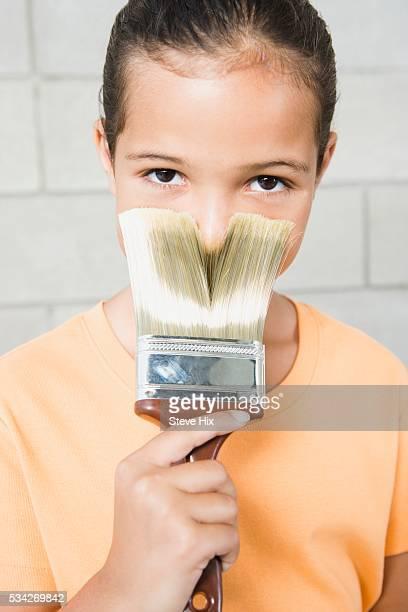 Girl Pressing Paintbrush Against Face
