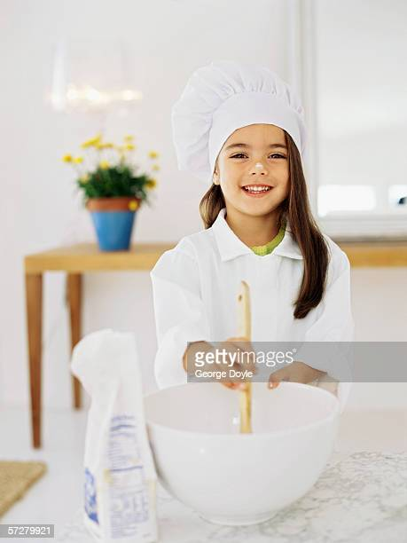 Girl pretending to be a chef, mixing ingredients in a bowl