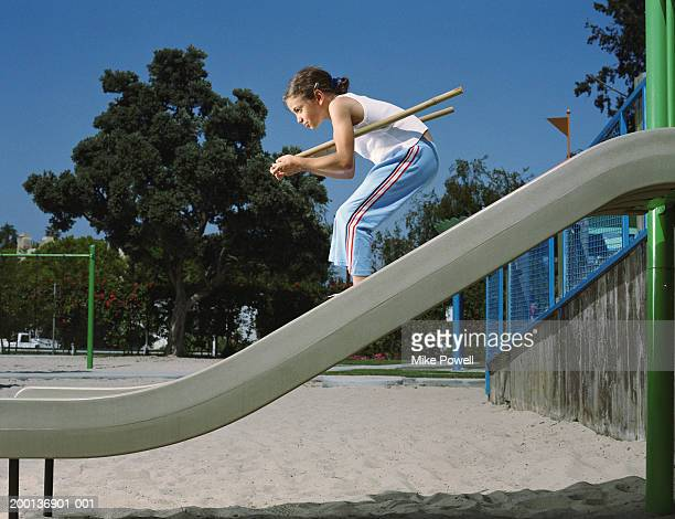 girl (8-10) pretending to be down hill skiing on playground slide - imagination stock pictures, royalty-free photos & images