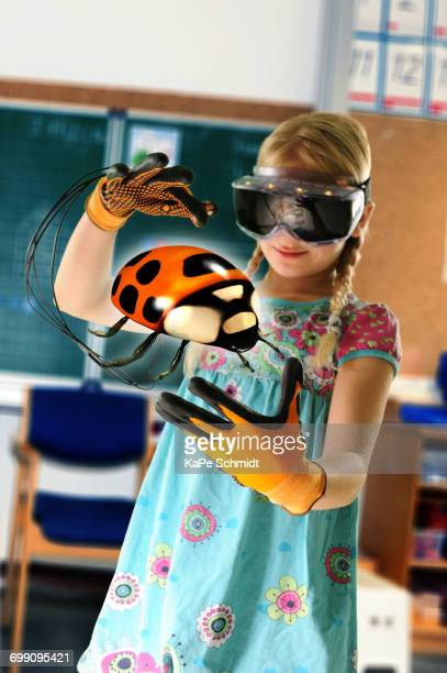 Girl pretending to be teacher wearing virtual reality headset and gloves to show ladybird