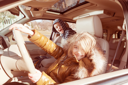 Girl pretending to drive car, brother in backseat - gettyimageskorea
