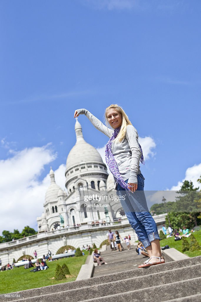 Girl pretending to hold top of monument : Stock Photo