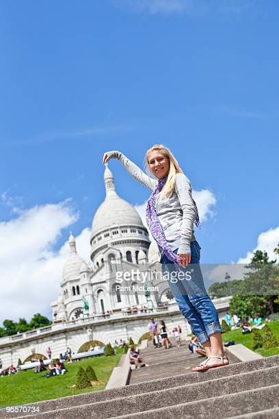 Girl pretending to hold top of monument
